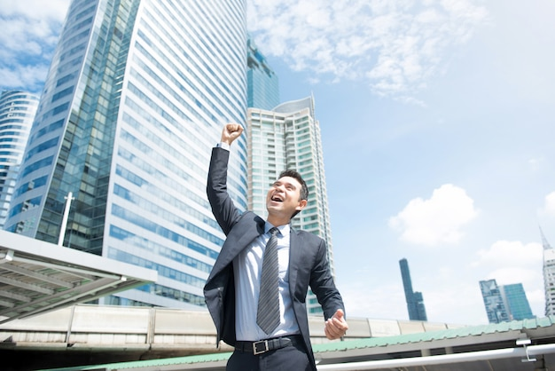 Businessman smiling and raising his fist in the air
