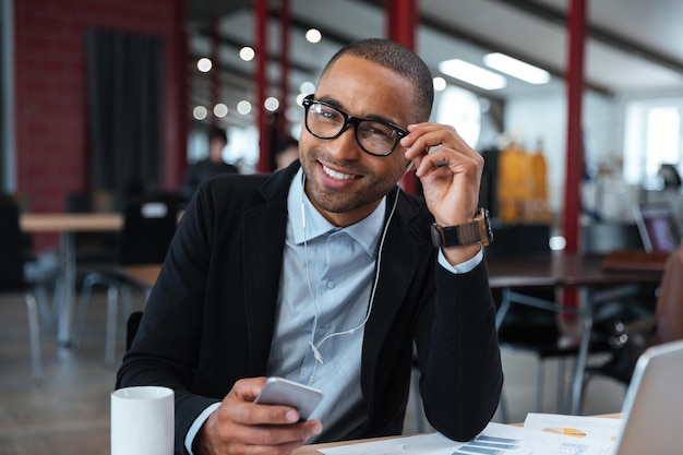 Businessman smiling and touching his glasses at the laptop