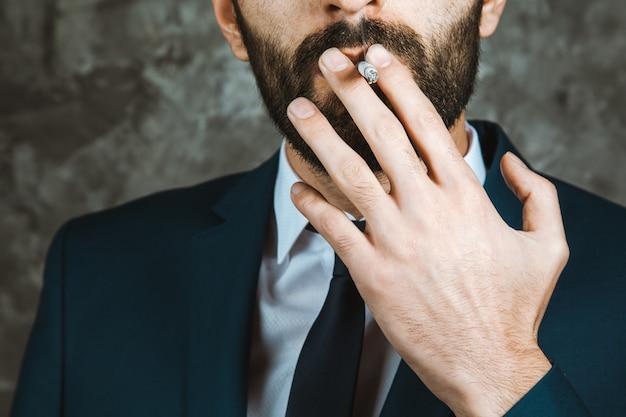 Бизнесмен курит сигарету на темном фоне