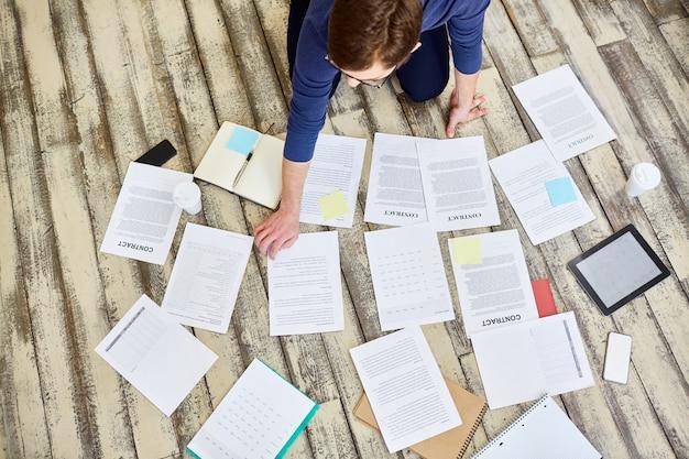 Бизнесмен, сортировка документов на деревянный пол