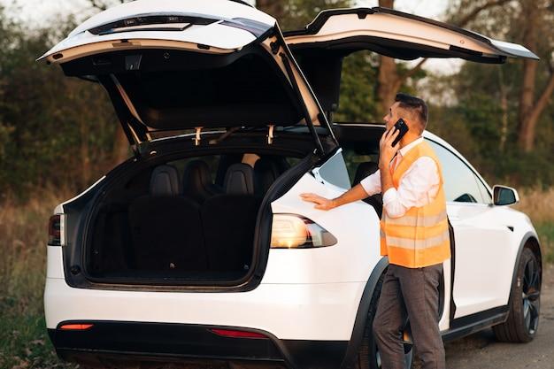 ビジネスマンは壊れた電気自動車の近くで電話で話します