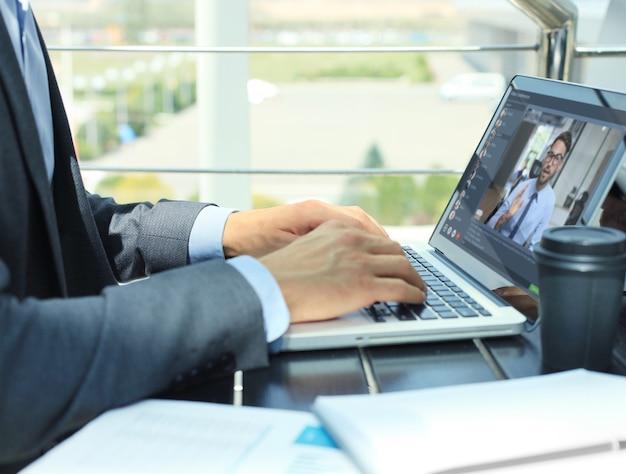 사업가는 자가 격리 및 격리 기간 동안 온라인 브리핑에 대해 동료들과 화상 통화로 이야기합니다. 사무실에서 노트북으로 동료들과 웹캠 그룹 회의.