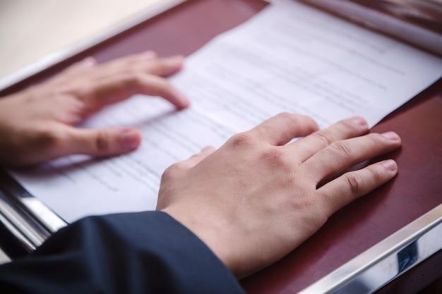 Спикер бизнесмен, стоя на подиуме с бумагами в руке