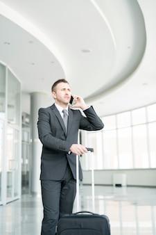 空港で電話で話すビジネスマン