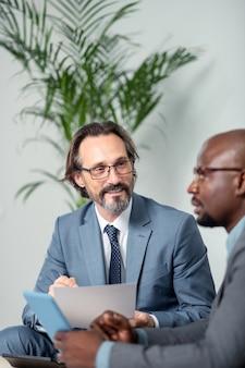 사업가 말하기. 작은 태블릿을 들고 동료와 말하는 안경을 쓴 회색 머리 사업가