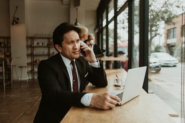 カフェで彼の電話で話すビジネスマン