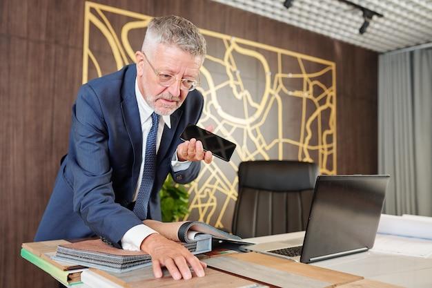 新しいオフィスのテーブルに木製の椅子を選ぶときにスピーカーフォンで話すビジネスマン