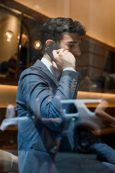 Businessman speaking on phone in cafe