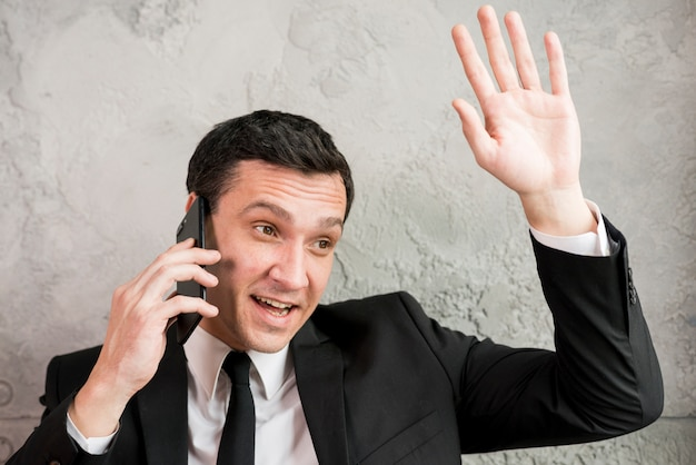 Businessman speaking on phone and waving hand