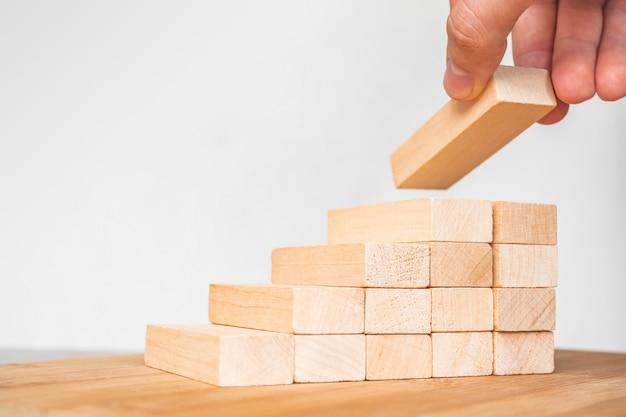 나무 블록을 쌓는 사업가. 손으로 나무 블록 쌓기를 계단식으로 배열합니다. 비즈니스 성장 성공 프로세스를 위한 사다리 경력 경로 개념