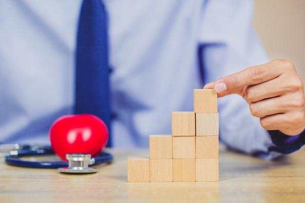Бизнесмен укладки деревянных блоков в шаги. концепция успеха роста бизнеса
