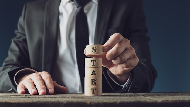 Businessman stacking wooden cut circles to assemble the word start in a conceptual image.
