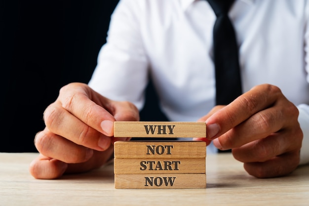 Businessman stacking wooden pegs to assemble the why not start now sign in a conceptual image.