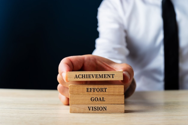 Бизнесмен укладывает деревянные колышки с элементарными словами для успеха в бизнесе - видение, цель, усилия и достижения. на синем фоне.
