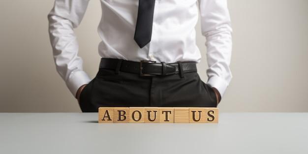 Бизнесмен, стоя за столом с надписью «о нас», собранной с деревянными кубиками.