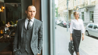 Businessman standing by cafe window near woman walking on sidewalk