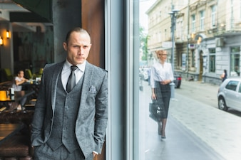 Businessman standing by cafe window