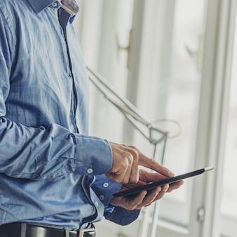 Бизнесмен, стоя у окон офиса, просматривая на своем цифровом планшете.