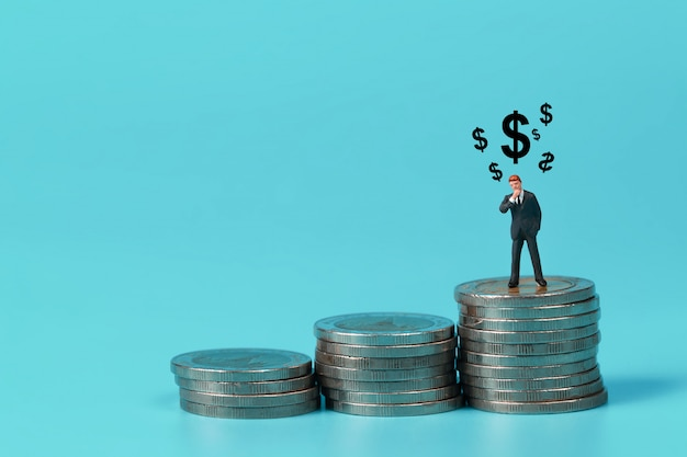 Businessman standing on coin stacking podium with dollar sign symbol