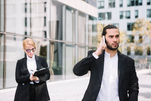 Businessman standing in front of busy businesswoman talking on cell phone