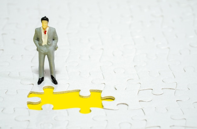 Businessman standing in front of  missing piece jigsaw on the yellow background.