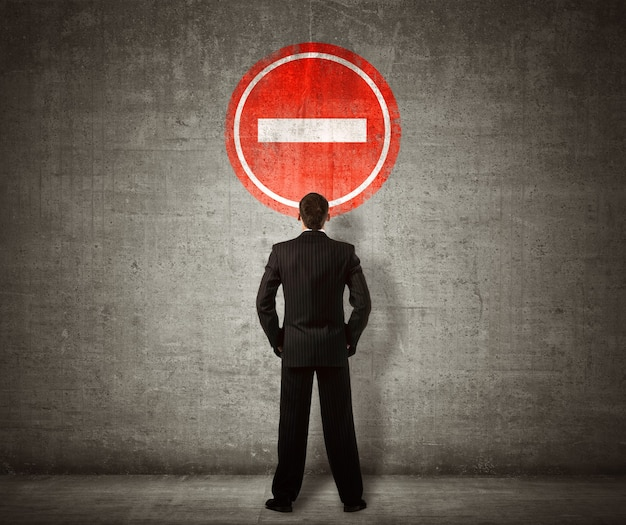 Businessman standing in front of no entry sign