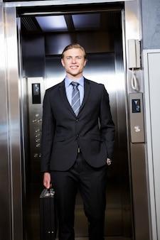 사무실에서 엘리베이터에 서있는 사업가
