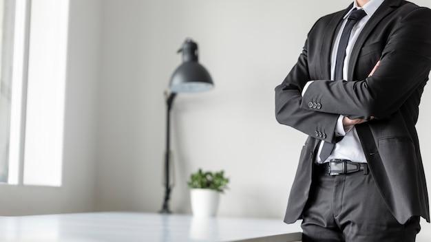 組んだ腕をオフィスに立っているビジネスマン