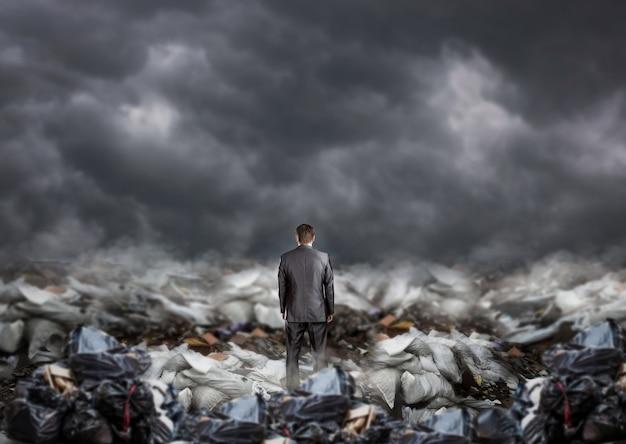 매립지, 다시보기, 쓰레기 더미 한가운데 서있는 사업가. 환경 사업 및 생태 오염 문제 프리미엄 사진