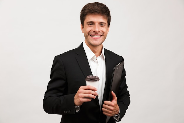 Businessman standing isolated holding clipboard drinking coffee.