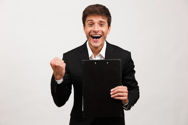 Businessman standing isolated holding clipboard making winner gesture.