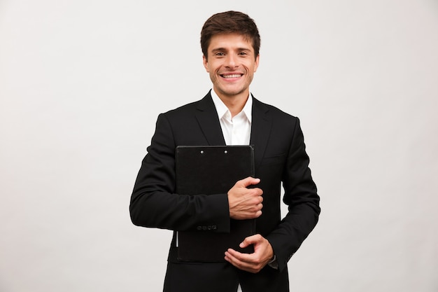 Businessman standing isolated holding clipboard
