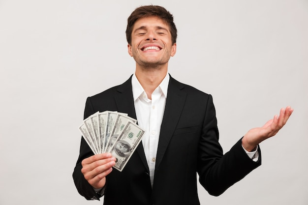 Businessman standing isolated holding money.