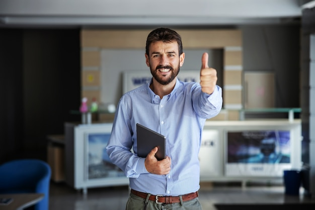 Businessman standing in lobby of export firm, holding tablet and showing thumbs up.
