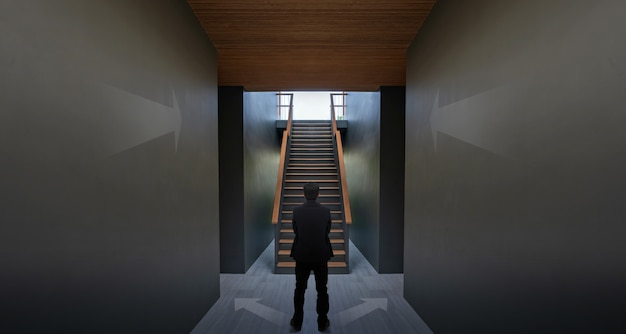 Businessman standing near arrow on black wall and staircase, concept of achieving your success