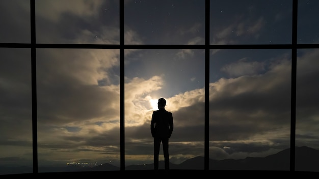 The businessman standing near the panoramic window on grey sky background