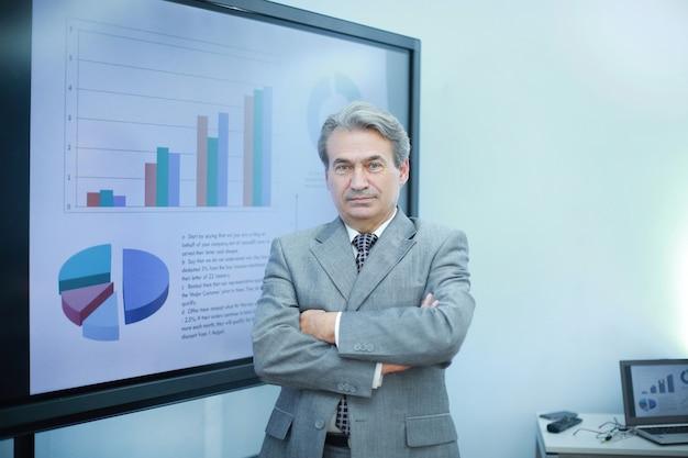 財務チャートで大画面の近くに立っているビジネスマン