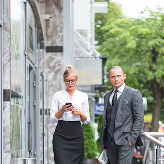 Businessman standing near woman using mobile phone