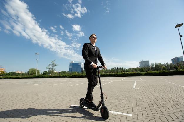 Бизнесмен стоит рядом с электрическим самокатом