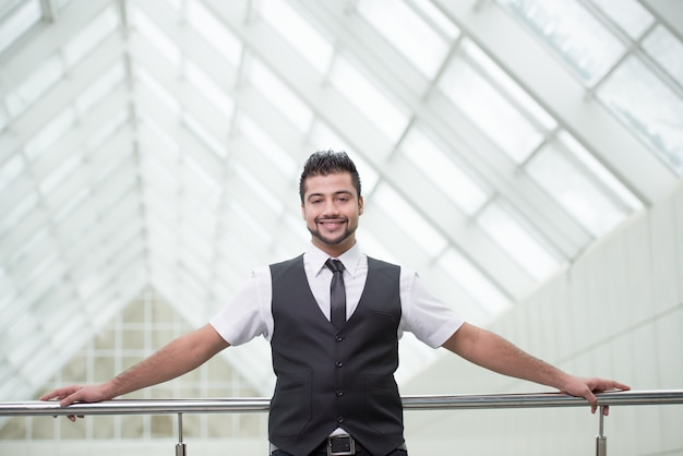 Businessman standing on office and smile.
