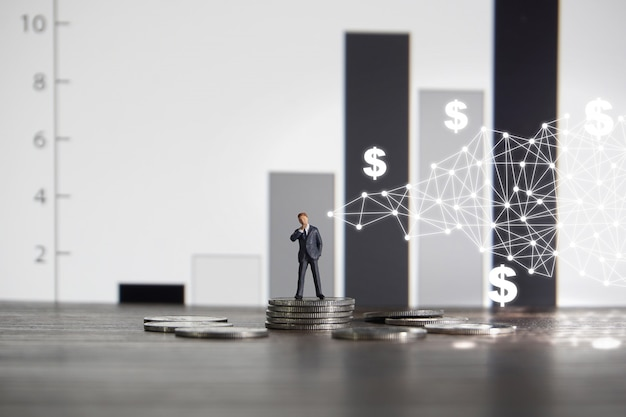 Businessman standing on a pile of coins