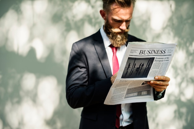 Businessman standing and reading newspaper
