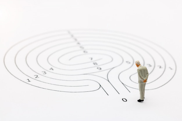 Businessman standing on start point of maze and  thinking how to solve this problem.