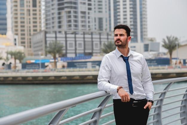 Businessman standing thinking near river.