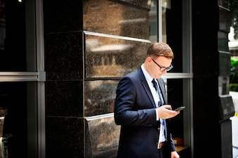 Businessman standing using mobile phone