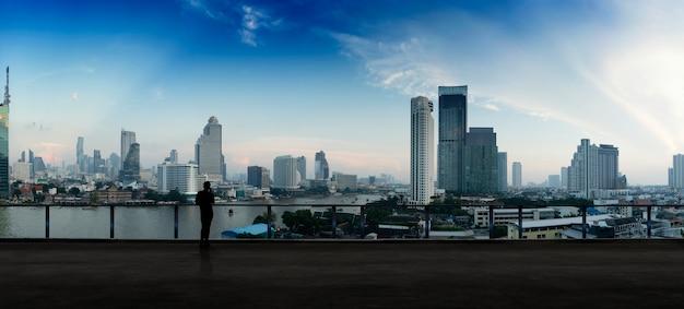 都市の夜景を見ているオープンルーフトップバルコニーにスマートフォンを使用して立っているビジネスマン。野望とビジョンとビジネス。