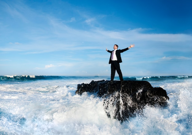 Businessman standing in a wavy sea