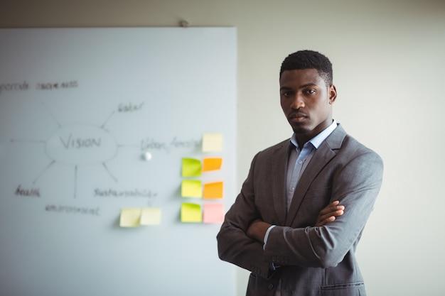 腕を組んでオフィスで立っている実業家