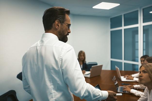 Бизнесмен, стоя спиной на переднем плане, обсуждает с командой, работающей за большим столом