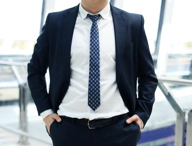 Бизнесмен, стоя с руками в карманах